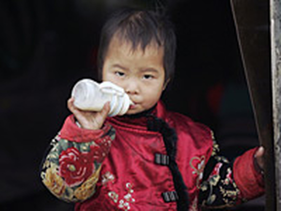 A young child drinks milk outside his home in Beijing. Milk consumption in China has tripled in just eight years.