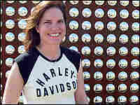 Harley-Davidson Museum Director Stacey Schiesl stands in front of a wall of rivets.