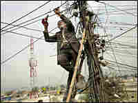 A power plant worker cuts old power lines in Kabul