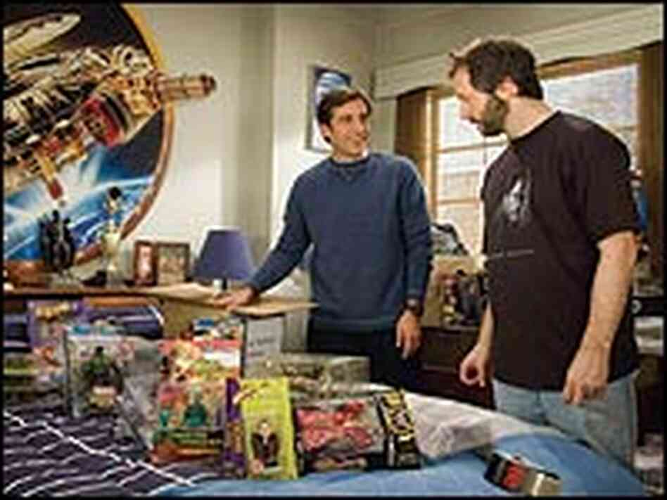 Steve Carell and Judd Apatow look over Star Wars figurines.
