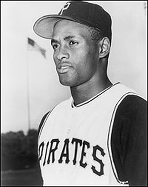 Roberto Clemente in baseball cap and uniform as a Pittsburgh Pirate rookie in 1955.