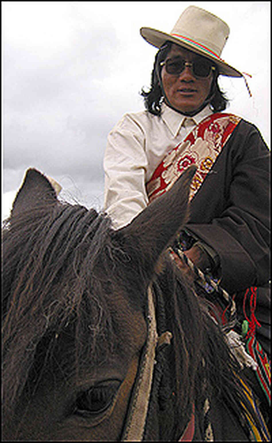 Typical attire for a Khampa horseman includes a western-style shirt under a Tibetan robe.