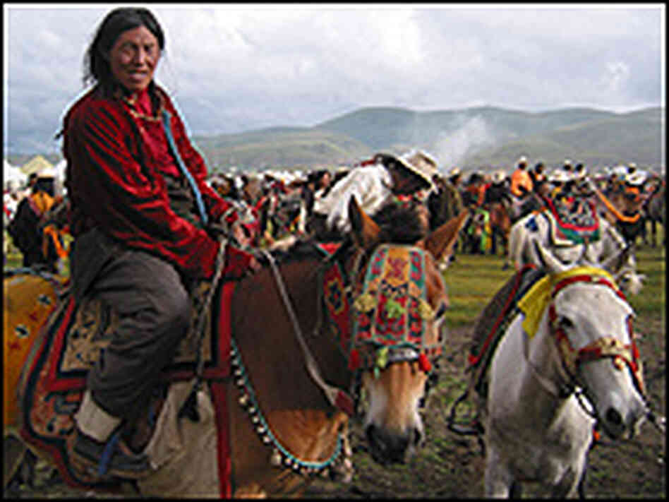 A Khampa horsemen saddles up for an initial charge opening the annual Litang Horse Festival.
