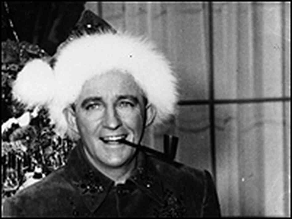 Bing Crosby in a Santa hat, smoking a pipe, in a 1954 photo.