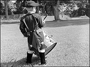 The youngest member of the Fife & Drum Corps of Chester, Conn., doing a three-beat roll on a drum.