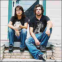 Tessie Brunet and Dax Riggs sit on steps outside a small house.