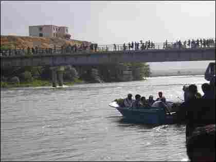 A boat full of passengers is launched as crowds look on.
