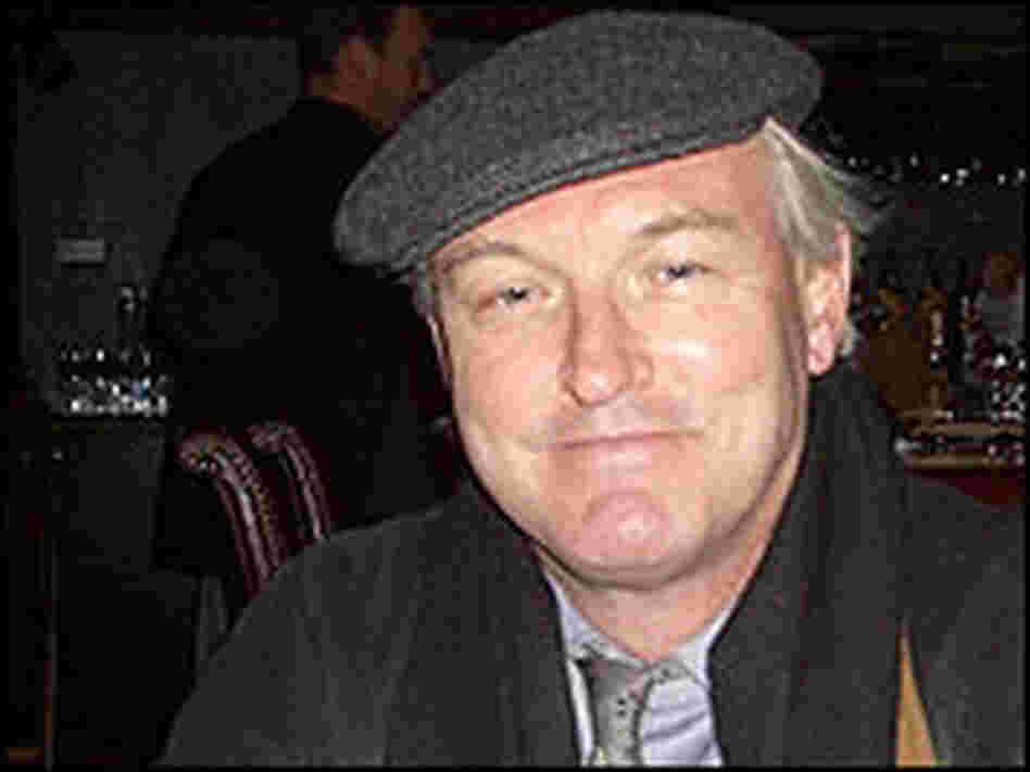 Christopher Buckley, photographed wearing a cap inside a dark bar.