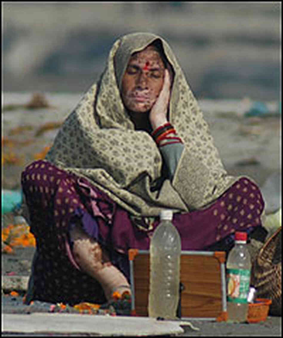 A woman with a skin disease rests near offerings and trash on the banks of the Ganges.