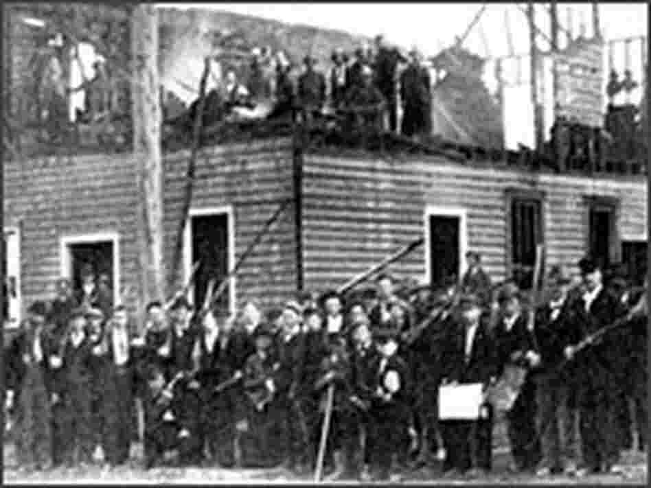 White men posed at a charred building in Wilmington, N.C.