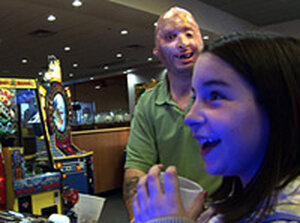 Sgt. Henline plays video games with his daughter. John Poole/NPR