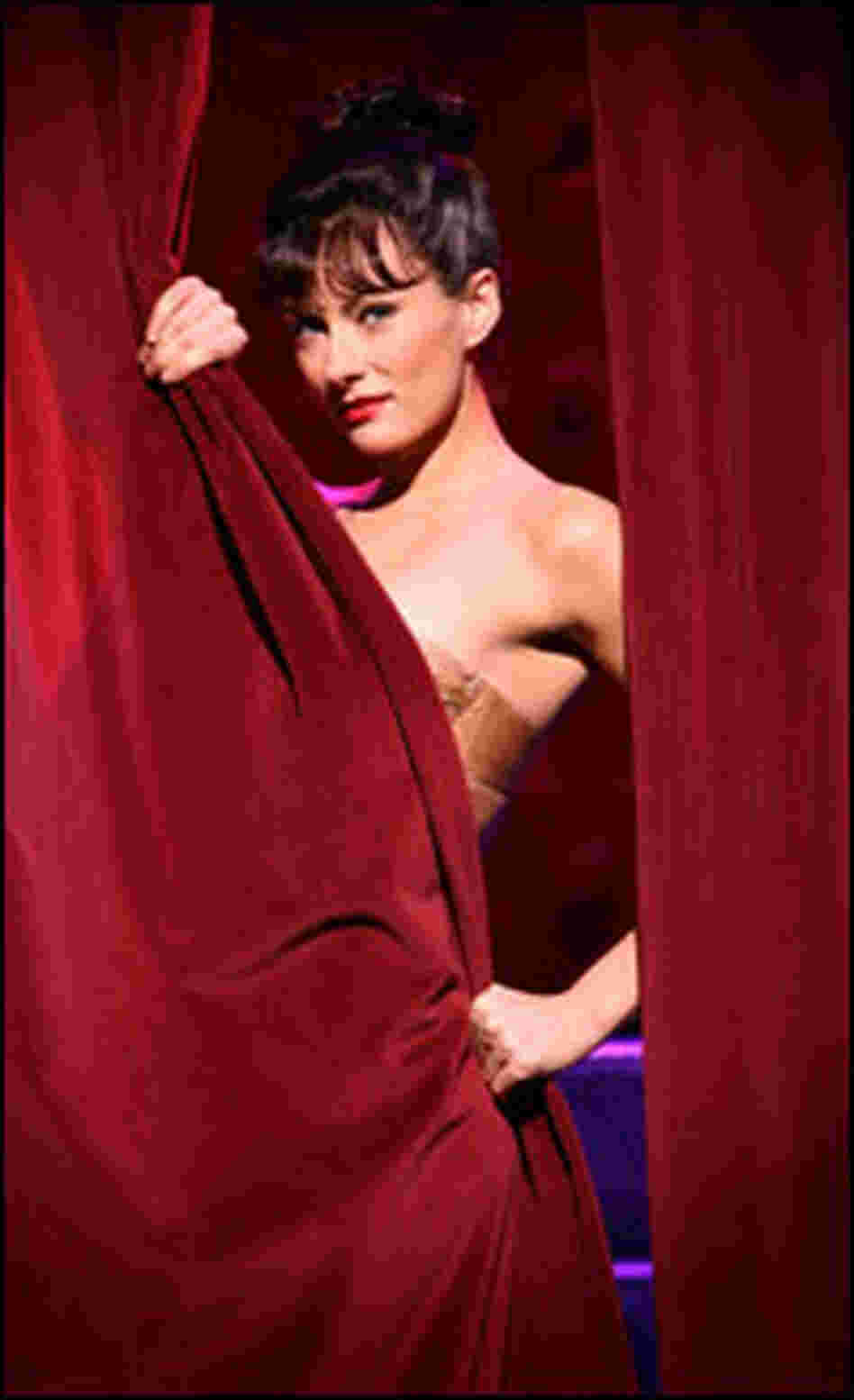 Laura Benanti peeks from behind a curtain