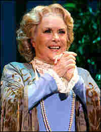 Howes as Mrs. Higgins, clasping her hands.