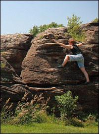 Kij Johnson climbing a large rock.